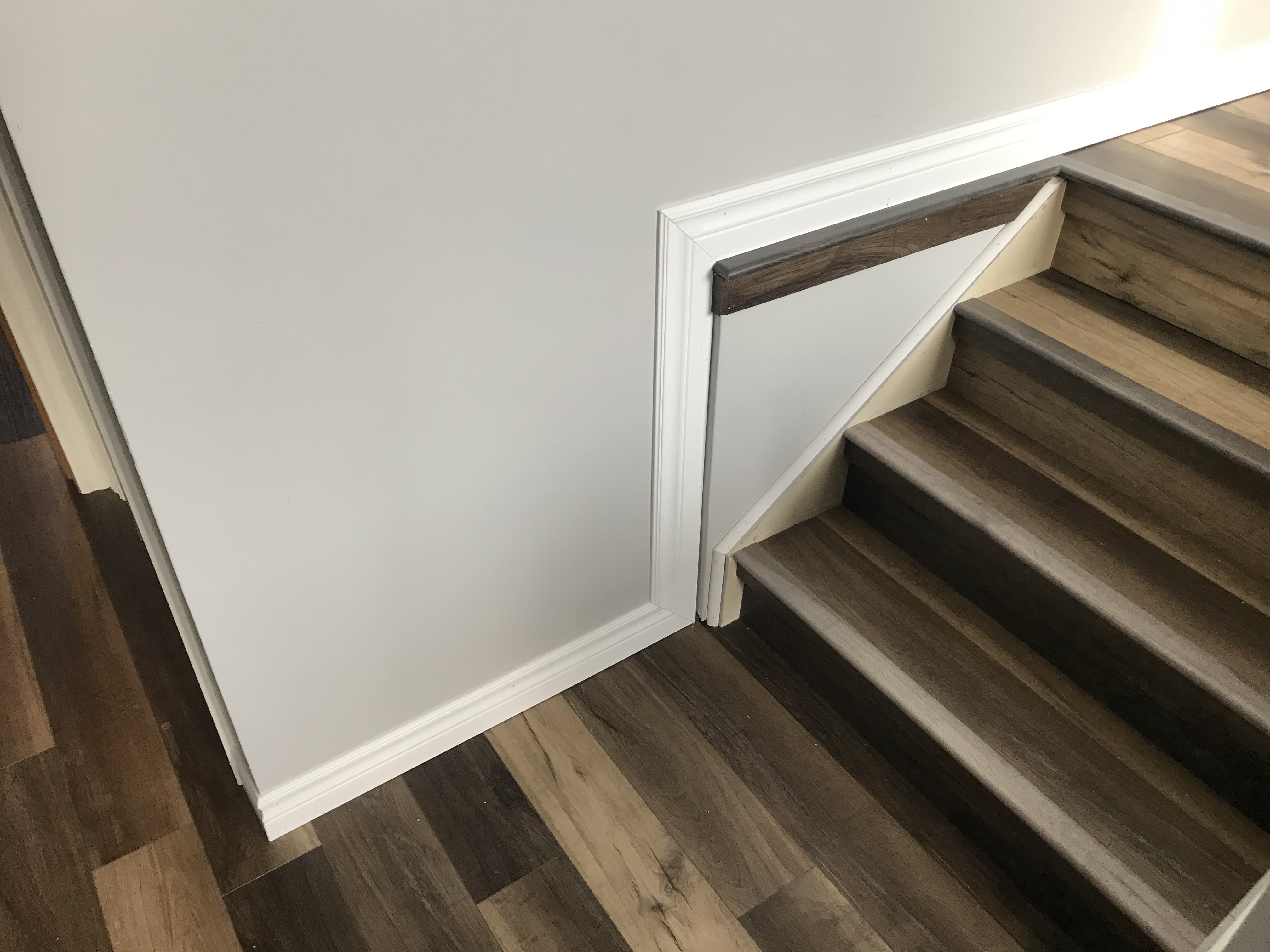 Trim work can sometimes require creative solutions.  Here, trim wraps around an awkward bump-out, while reused laminate flooring ties it all together.