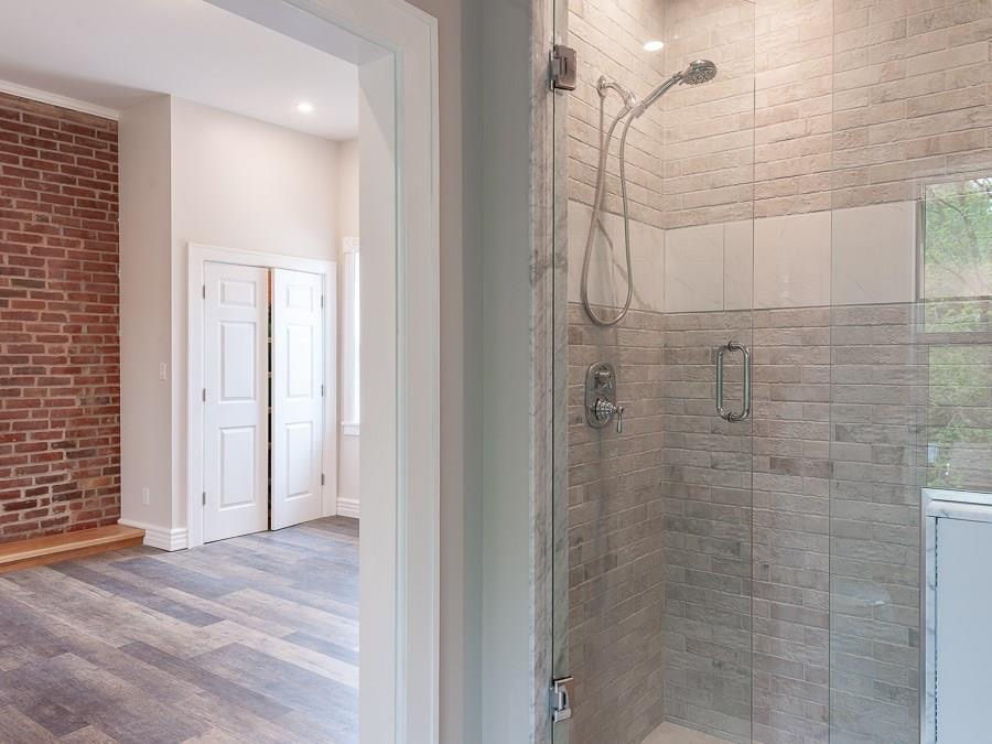 Many character elements are shown here:  tilework in a custom shower, millwork that blends old and new, and restored original brick, all blended with brand-new flooring.