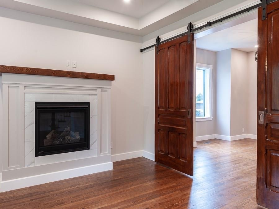 The original pocket doors were removed, restored, and converted into barn doors with custom tracks and a custom jamb, complimenting the tile and lighter tones of the site-built fireplace surround. The mantle was crafted by hand, repurposed from original floor joist.