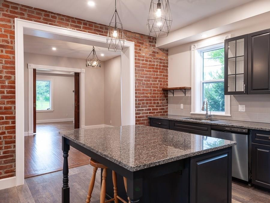 The opening in this original brick wall was widened to 3x the original size, and all the brick was repointed, establishing a focal point for the kitchen.  The backsplash tile plays against the geometry of the brick, while a window was restored to its original size to increase natural light.