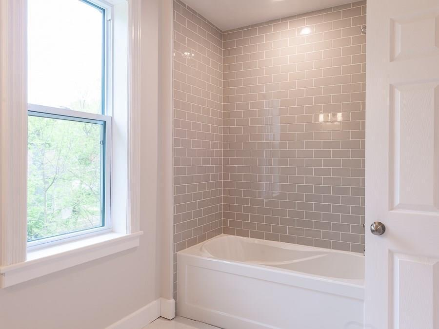 Instead of a prefabricated tub surround, tilework extends from the bath all the way to the 9 foot ceiling in this custom tub/shower combo.  Vintage, reclaimed millwork on custom jambs ties the oversized window into the rest of the home.