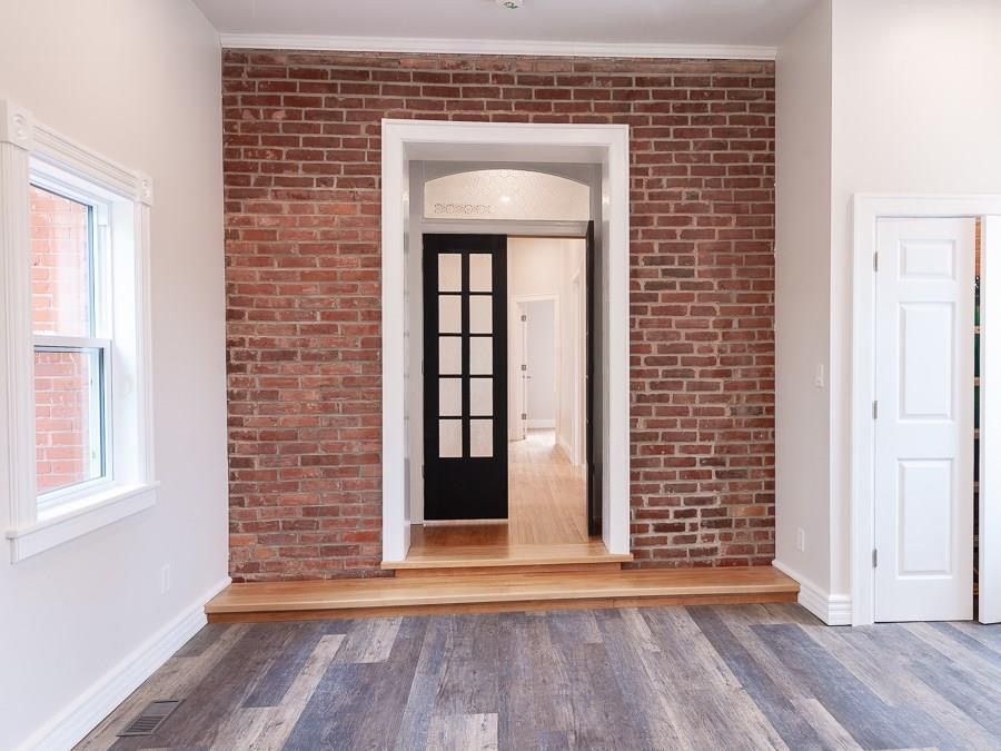 Creating a dramatic entrance to the master bedroom was the goal here, and we think it was achieved!  The exposed brick and restored transom window display the home's original character, while the double doors with vintage glass and millwork add a custom touch.